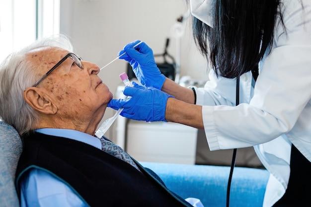 Pielęgniarka w niebieskich rękawiczkach sanitarnych podnosi głowę starszego mężczyzny w niebieskiej koszuli i krawacie, aby wykonać test na obecność wirusa covid, kiedy ten siedzi na kanapie w domu. domowa opieka zdrowotna.