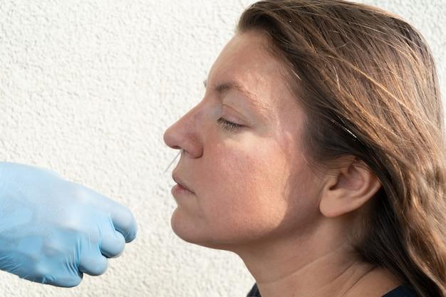 Pielęgniarka w niebieskich rękawiczkach wykonuje test na wirusa koronowego nosa kobiecie