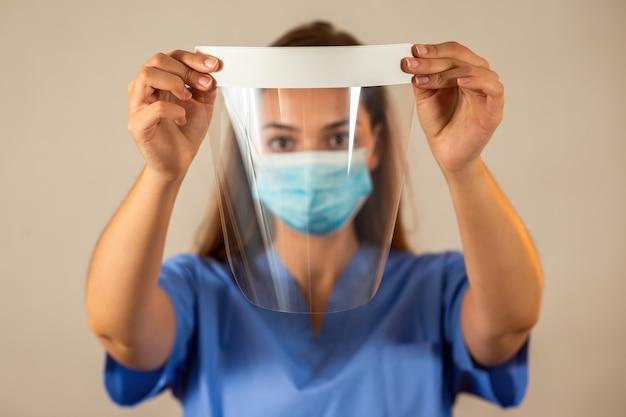 Pielęgniarka w niebieskiej koszuli, trzymając osłonę twarzy przed nią