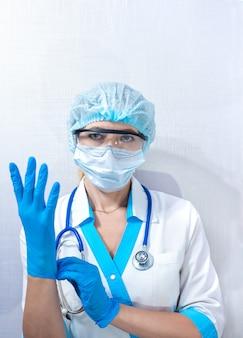 Pielęgniarka w odzieży ochronnej zakłada gumowe rękawiczki, środki ochrony osobistej w walce z chorobami