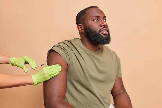 Pielęgniarka w rękawiczkach medycznych robi pacjentowi zastrzyk przeciwwirusowy