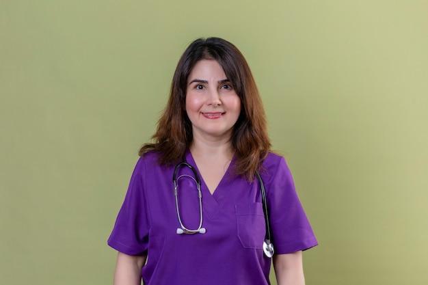Pielęgniarka w średnim wieku kobieta ubrana w mundur i stetoskop patrząc na kamery pozytywne i szczęśliwe uśmiechnięte przyjazne stojących na zielonym tle