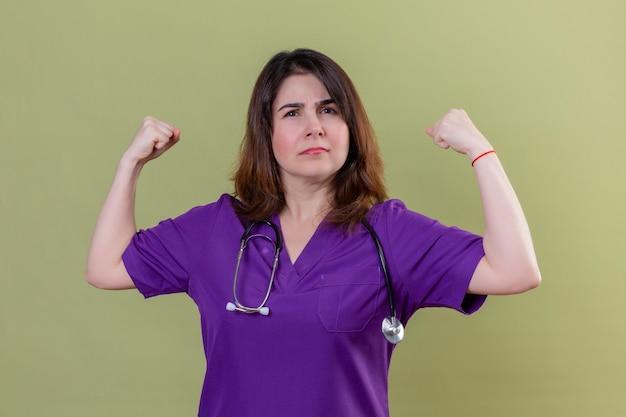 Pielęgniarka w średnim wieku, ubrana w mundur i stetoskop, wyglądająca na pewną siebie zadowoloną z siebie, radująca się ze swojego sukcesu i zwycięstwa, zaciskająca pięści z radości, szczęśliwa z osiągnięcia celu i celów s