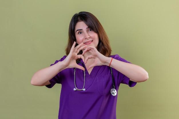 Pielęgniarka w średnim wieku ubrana w mundur i ze stetoskopem wykonująca romantyczny gest serca na klatce piersiowej patrząc na kamerę z uśmiechem na twarzy stojącej na odizolowanym zielonym tle