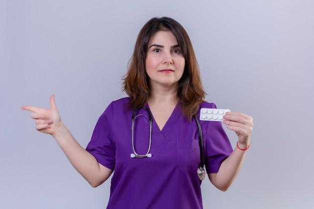 Pielęgniarka w średnim wieku ubrana w mundur medyczny i ze stetoskopem trzymająca blister z tabletkami patrząc na kamerę z poważną twarzą wskazującą palcem w bok stojącą nad białym backgrou