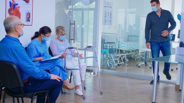 Pielęgniarka w szpitalnej poczekalni z maską przeciw covid-19 pomaga nieważnej starszej kobiecie wypełnić dokumenty. lekarz zaprasza starego człowieka w sali egzaminacyjnej. system opieki zdrowotnej podczas globalnej pandemii