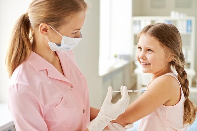 Pielęgniarka wstrzykiwanie uśmiechniętą dziewczynę