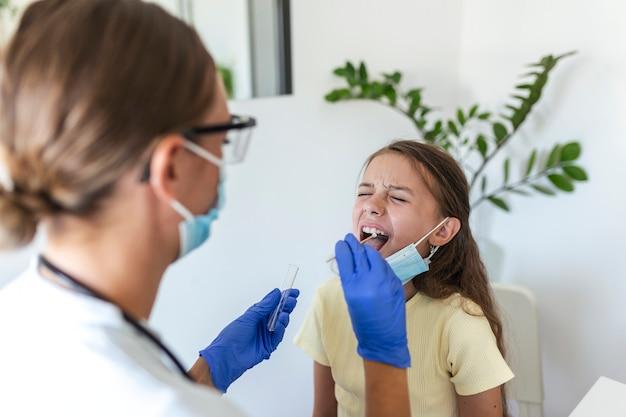 Pielęgniarka wykonująca badanie wymazu z ust u małego dziecka. dziewczyna przechodząca testy pcr z powodu pandemii covid-19. lekarka za pomocą wacika podczas badania pcr małej dziewczynki