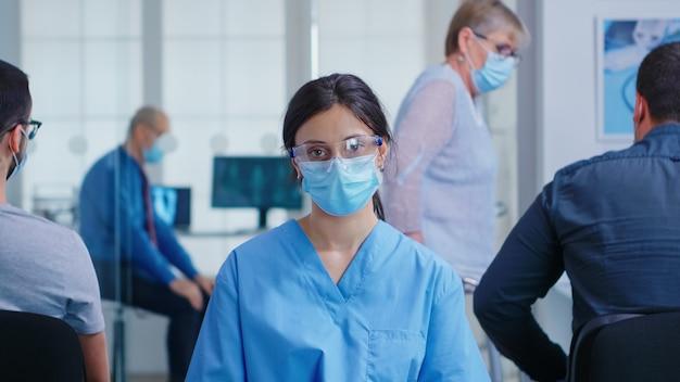 Pielęgniarka z maską na twarz przed koronawirusem w poczekalni szpitala patrząc na kamery. starsza kobieta z niepełnosprawnością chodzenia przy użyciu ramki zimmer.