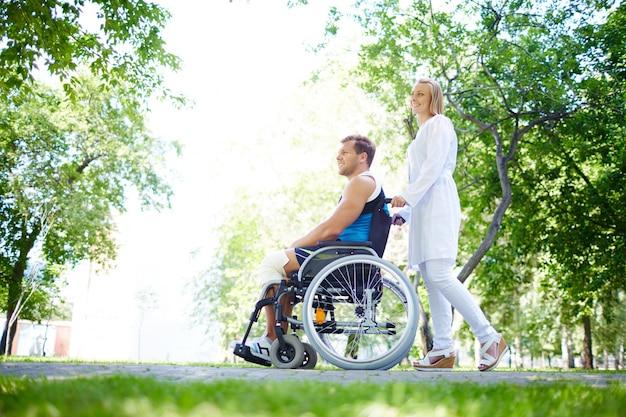 Pielęgniarka z młodym mężczyzną w wózku