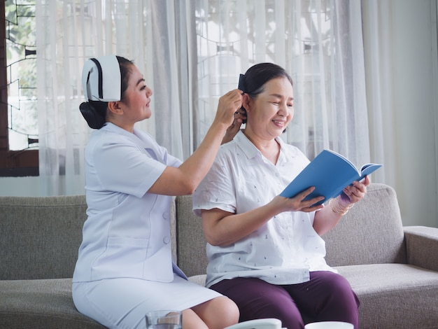 Pielęgniarka z radością przeczesuje włosy osobom starszym, stara kobieta czyta książkę
