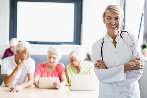 Pielęgniarka z rękami skrzyżowanymi przed seniorami