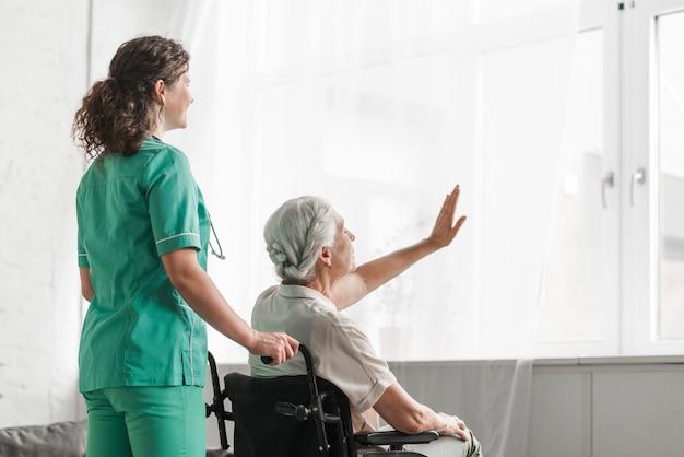 Pielęgniarka z starszy kobieta siedzi w wózku inwalidzkim, dotykając biały kurtyny