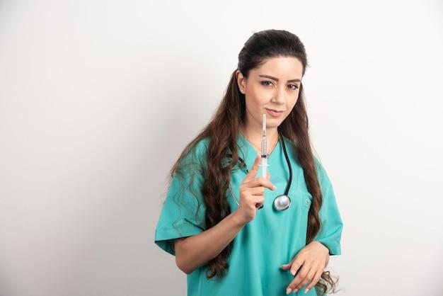 Pielęgniarka z stetoskopem trzyma zastrzyk.