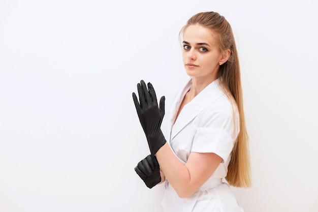 Pielęgniarka zakłada czarne gumowe rękawiczki na białym tle