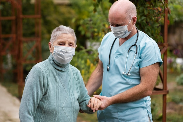 Pielęgniarki mężczyzna trzyma rękę starszej kobiety, aby pomóc jej chodzić