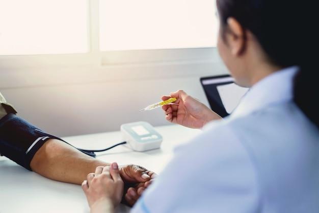 Pielęgniarki mierzą ciśnienie i przeglądają pomiary temperatury ciała.