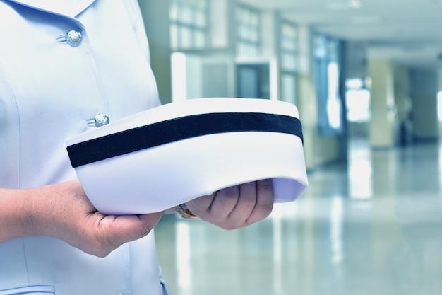 Pielęgniarki trzymają czapkę pielęgniarską. jednolite pojęcie opieki
