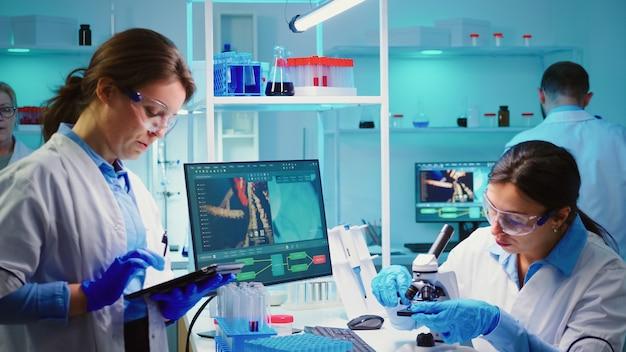 Pielęgniarki wspólnie analizujące mutacje wirusów pracujące w godzinach nadliczbowych w laboratorium wyposażonym w chemię