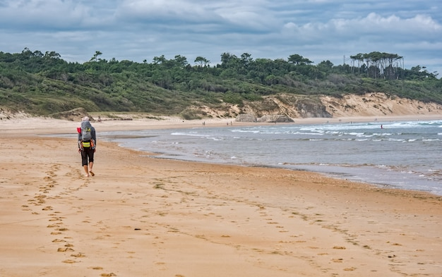 Pielgrzym z plecakiem idący na plażę po północnej drodze camino de santiago, hiszpania