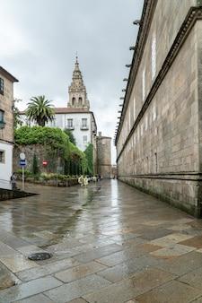 Pielgrzymi i turyści spacerujący ulicą starego miasta santiago de compostela w deszczowy dzień
