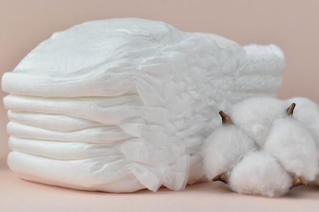 Pieluchy dziecięce i suszona bawełna na beżowym zbliżeniu.