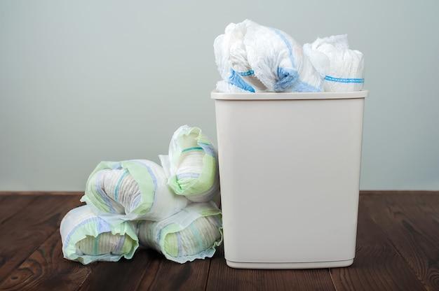Pieluchy wyrzucają brudne pieluchy do kubła na śmieci wyrzucanie zużytych pieluszek dziecięcych wpływ pieluch jednorazowych na środowisko zanieczyszczenie środowiska, gleby i wody