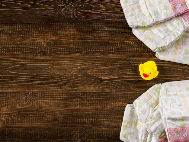 Pieluszki i gumowe kaczątko na drewniane tła