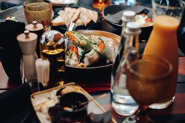 Pień fotografia bułki warzywne z ogórkiem, marchewką i zieleniną w papierze ryżowym podawane na talerzu na stole w restauracji.