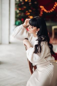 Pień fotografia eleganckiej zamyślonej dziewczyny z długimi ciemnymi włosami na sobie beżowy sweter i jedwabną spódnicę patrząc w dół zamyślony siedząc na krześle.