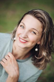 Pień fotografia headshot z atrakcyjną młodą kobietą z farbowanych włosów średniej długości z czerwonymi ustami i kolczykami uśmiecha się do kamery ze szczęścia. niewyraźne tło.