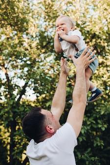 Pień fotografia kochającego ojca rzucając syna w powietrze przed wielkim zielonym drzewem w słońcu. szczęśliwy chłopiec z ojcem. koncepcja rodziny.