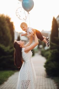 Pień fotografia kochającej matki w pięknej białej letniej sukience podnoszącej syna z nadmuchiwanymi balonami w powietrzu w pięknym ogrodzie w rozmytym tle. świętujemy urodziny syna na świeżym powietrzu.