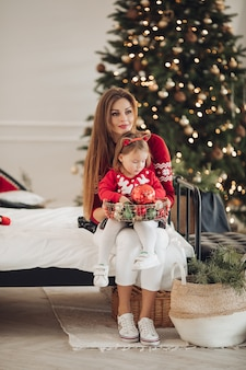 Pień fotografia kochającej matki w zielonej sukni, dając jej córeczkę w sukni piżamy prezent pod choinkę. są obok pięknie udekorowanej choinki pod śniegiem.