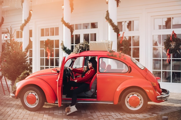 Pień fotografia ładnej kobiety w czerwonym swetrze siedzi w modnym czerwonym samochodzie. ozdoby świąteczne.