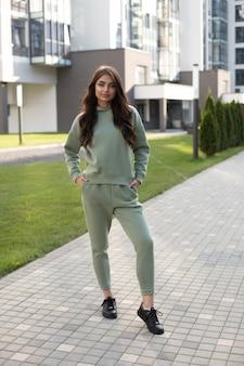 Pień fotografia młodej modelki z długimi falującymi włosami, ubranej w stylową bluzę i joggery z czarnymi skórzanymi butami, stojącą na nowoczesnej ulicy ze współczesnymi budynkami.