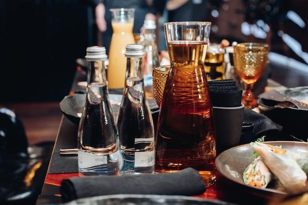 Pień fotografia pełnych szklanych butelek wody i słoik czystej wody niegazowanej na stole z serwowanym jedzeniem na bankiecie.