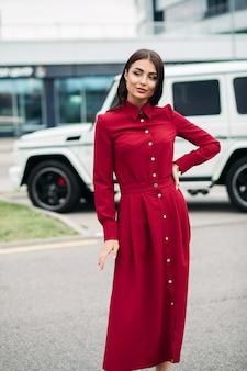 Pień fotografia pięknej młodej damy w jaskrawoczerwonej sukience z brązowymi włosami i makijażu uśmiechniętego podczas pozowanie z ręką na pasie na ulicy.