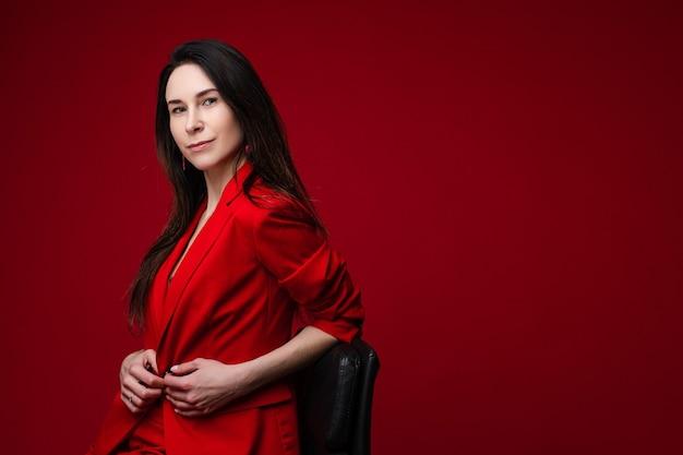 Pień fotografia portret przepiękny pewny siebie businesswoman z ciemnymi włosami w czerwonej kurtce siedzi na krześle i patrząc na kamery. wyizoluj na jasnoczerwonym tle. skopiuj miejsce.