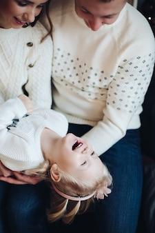 Pień fotografia portret szczęśliwych rodziców w białych swetrach łaskotanie ich córeczkę na kolanach. córka radośnie się śmieje. ozdoby świąteczne.