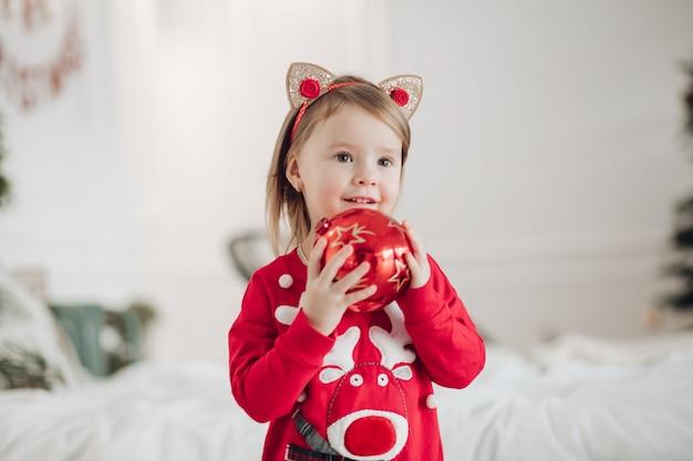 Pień fotografia portret uroczej dziewczyny w czerwonej sukience z świątecznym nadrukiem, trzymając pięknie zawinięty złoty prezent w rękach, siedząc na podłodze obok ozdobionej choinki z girlandą.
