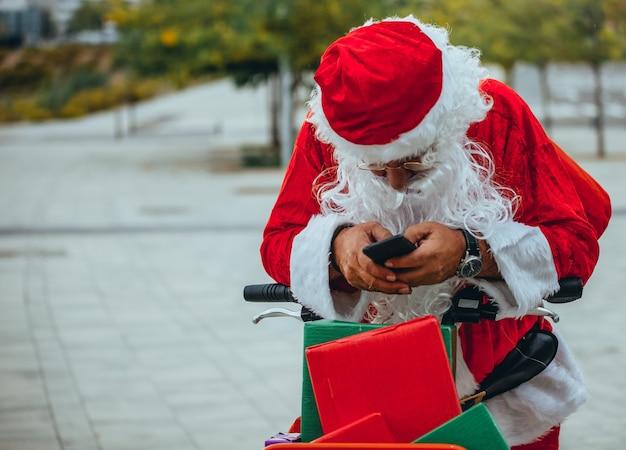 Pień fotografia przedstawiająca świętego mikołaja rozmawiającego z telefonem komórkowym w parku za nieostre