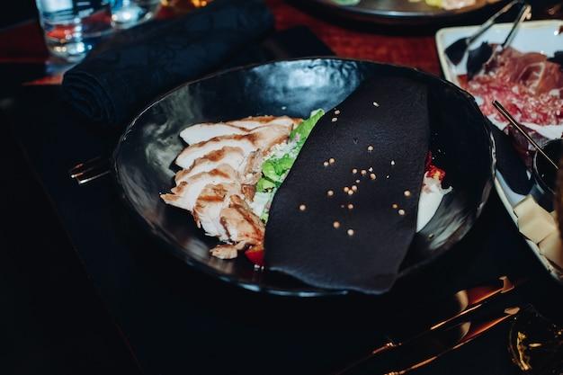 Pień fotografia pyszne świeże sałatki cezara z plastrami kurczaka podawane z czarnym plasterkiem z sezamem w misce na czarnym stole.