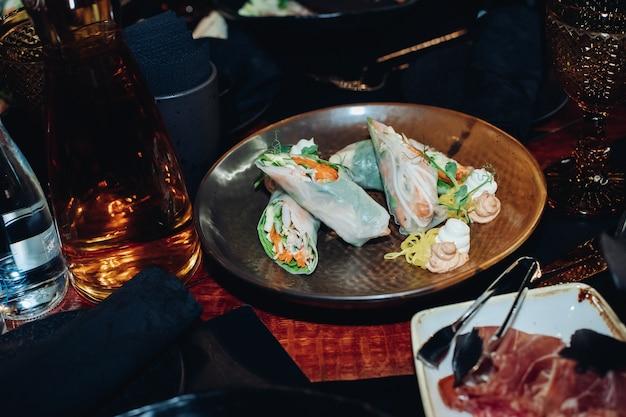 Pień fotografia pysznych świeżych bułek z surowymi warzywami i makaronem podawanych na talerzu z sosami i zieleniną.