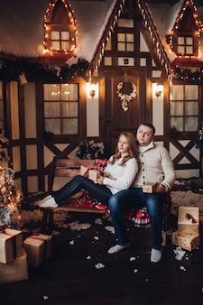 Pień fotografia romantycznej pary w ubranie, siedząc na ławce z owiniętymi prezentami i patrząc na udekorowane choinki