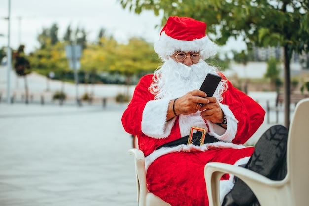 Pień fotografia świętego mikołaja siedzi na krześle z nogami do góry i patrząc na telefon komórkowy.
