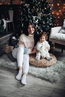Pień fotografia uśmiechnięta atrakcyjna matka i dziecko siedzi pod udekorowaną choinką w domu.