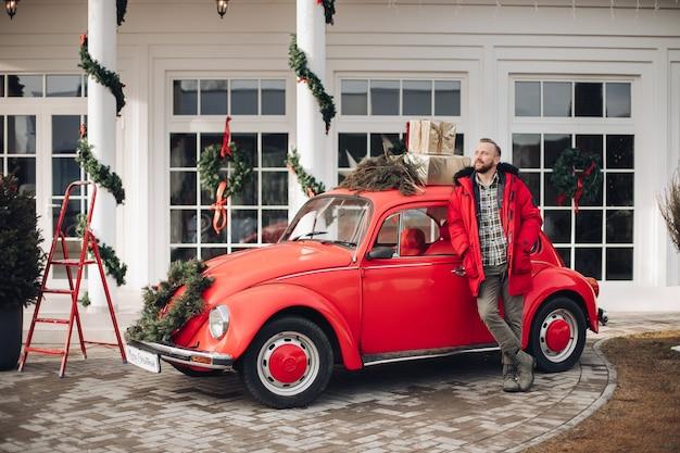 Pień fotografia z przystojnym, stylowym mężczyzną w czerwonej kurtce stojącej przez rocznika samochodu z dekoracjami świątecznymi.