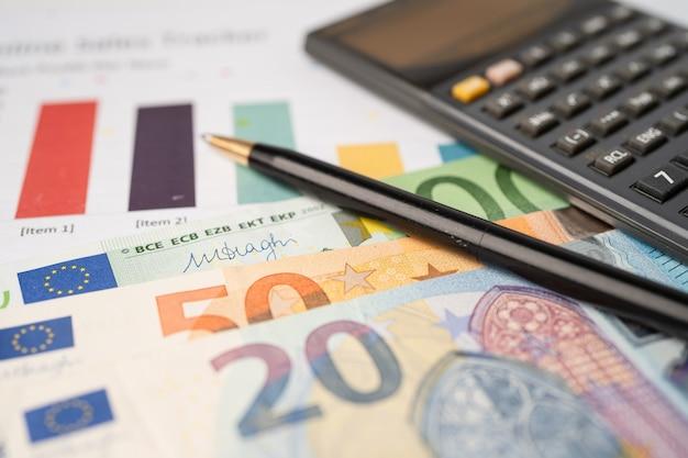 Pieniądze banknotów euro z kalkulatora na papierze milimetrowym.