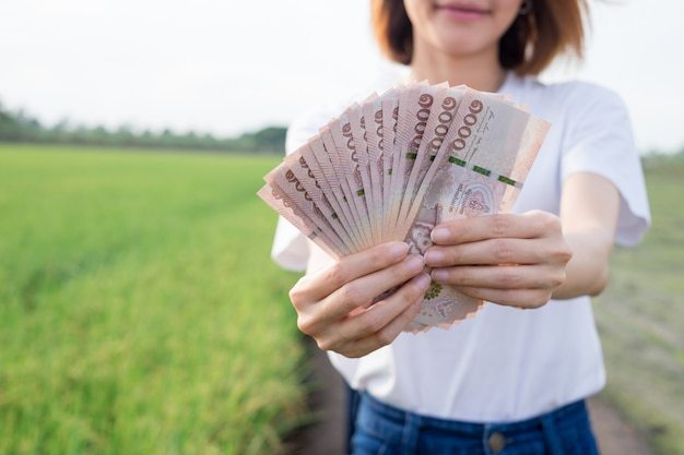 Pieniądze banknotów tajskich gospodarstwa przez podróżnika azjatyckiej kobiety na farmie zielonego ryżu